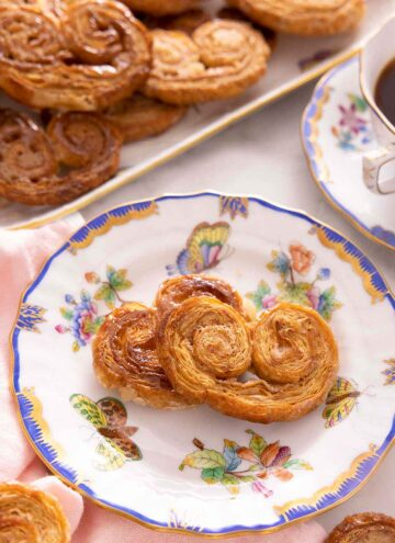 A plate with two palmiers in front of a platter with more.