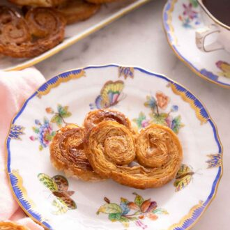 Pinterest graphic of a plate of two palmiers by a cup of coffee and a platter of more palmiers.