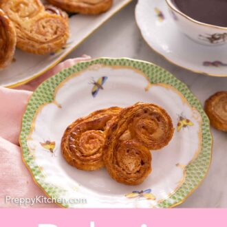 Pinterest graphic of a plate of palmiers with a platter of more in the back by a cup of coffee.
