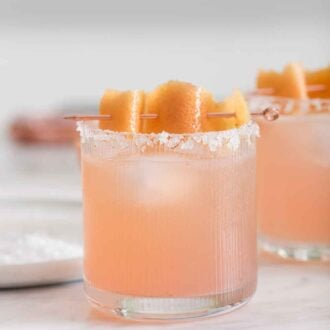 Pinterest graphic of a glass of paloma with a citrus peel for garnish.
