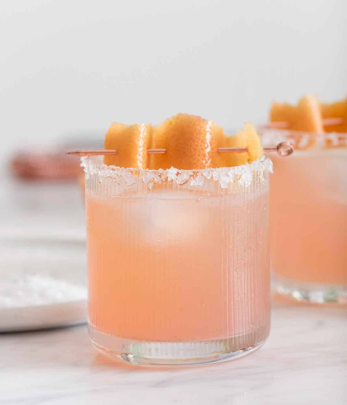 A glass of paloma with a salted rim with a grapefruit peel garnish on top.