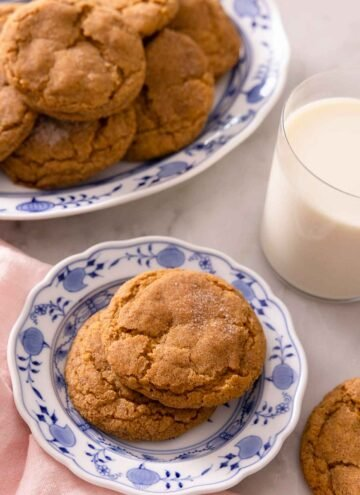 A plate with two pumpkin snickerdoodles with a larger plate containing more behind it with a glass of milk.