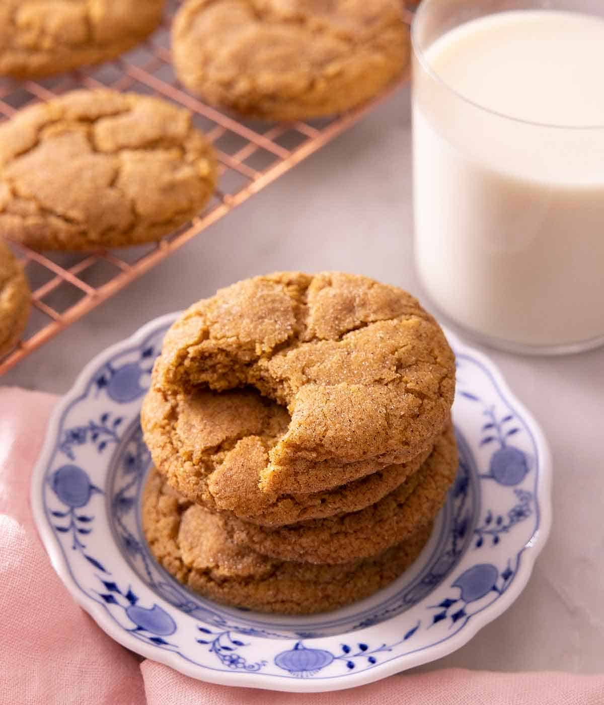 A plate with a stack of pumpkin snickerdoodles with one cookie missing a bite, beside a glass of milk.