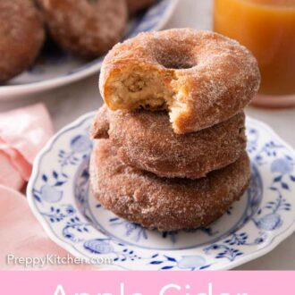 Pinterest graphic of a stack of three apple cider donuts on a plate, the top on with a bite taken out of it.