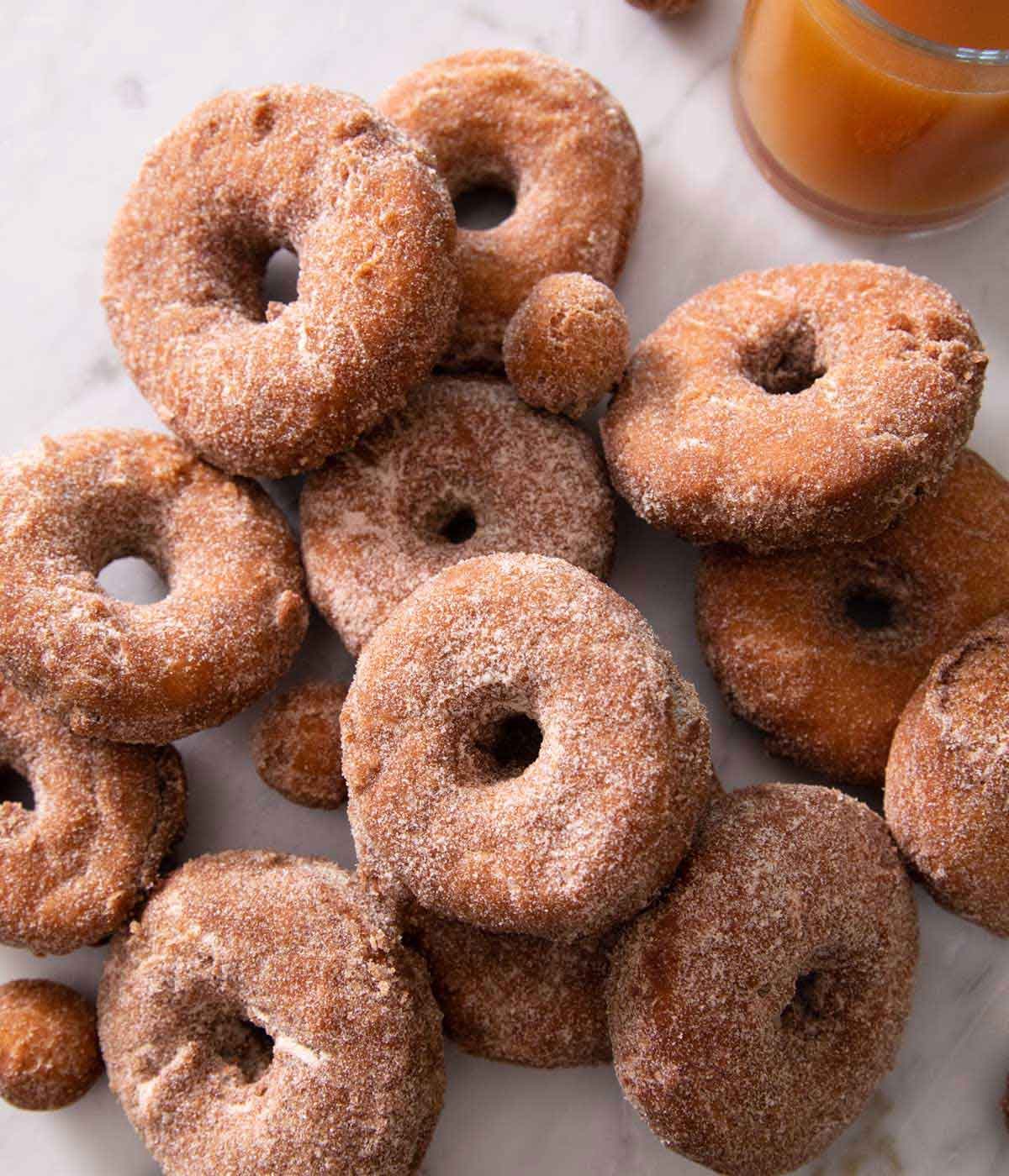 Multiple apple cider donuts piled on top of each other on a marble countertop.