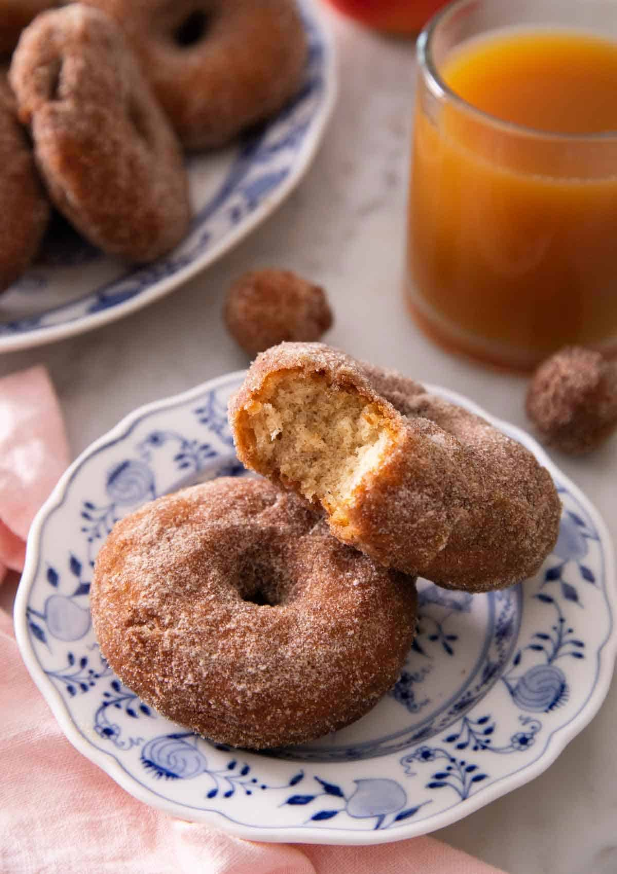 Two apple cider donuts, with one with a bite taken out of it, on a plate in front of a cup of apple cider.