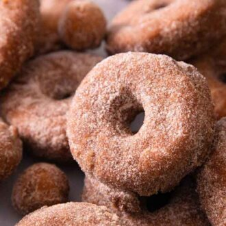 Multiple apple cider donuts and donut holes with one in focus in the middle.