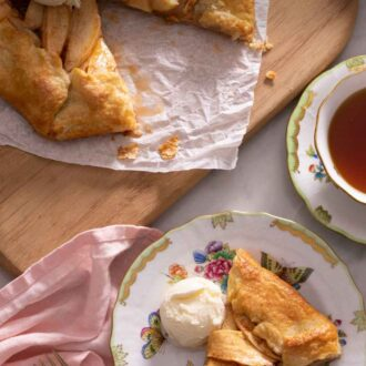Overhead view of a plate of a slice of apple galette with a scoop of ice cream beside the rest of the galette.