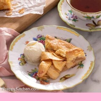 Pinterest graphic of a plate with a slice of apple galette with a scoop of ice cream in front of a cup of tea.
