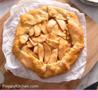 Pinterest graphic of an overhead view of an apple galette on a sheet of parchment paper on a wooden serving board.