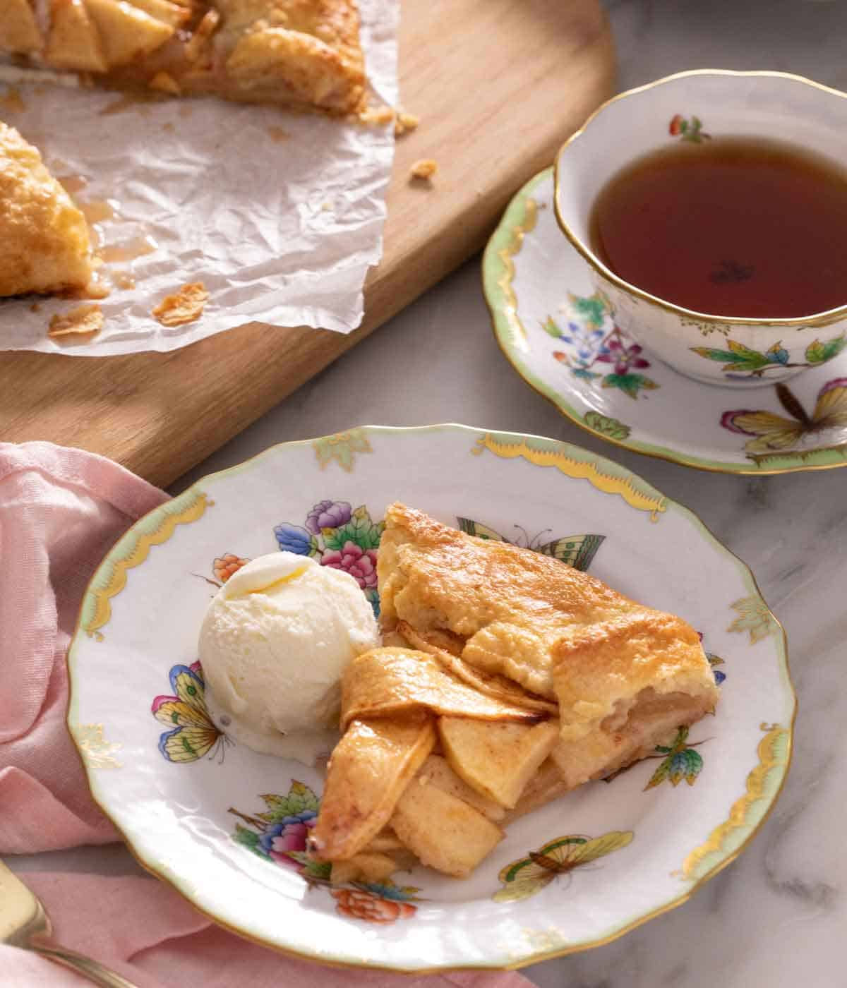 A plate with a slice of apple galette with a scoop of ice cream beside it in front of a cup of tea.