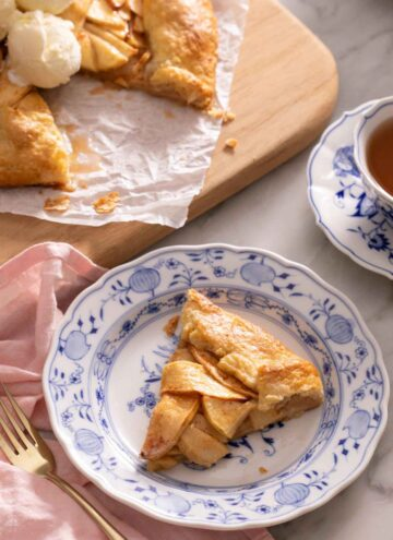 A plate with a slice of apple galette with a cutting board in the background with the rest of the galette along with a cup of tea.