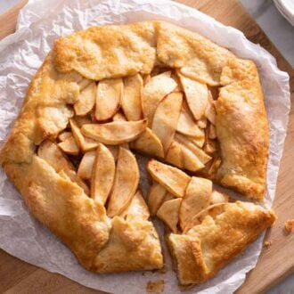 Overhead view of an apple galette with a slice cut but not removed from the serving board.