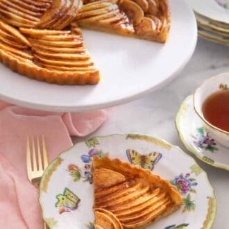 Pinterest graphic of a slice of apple tart in front of a serving stand with the rest of the tart.