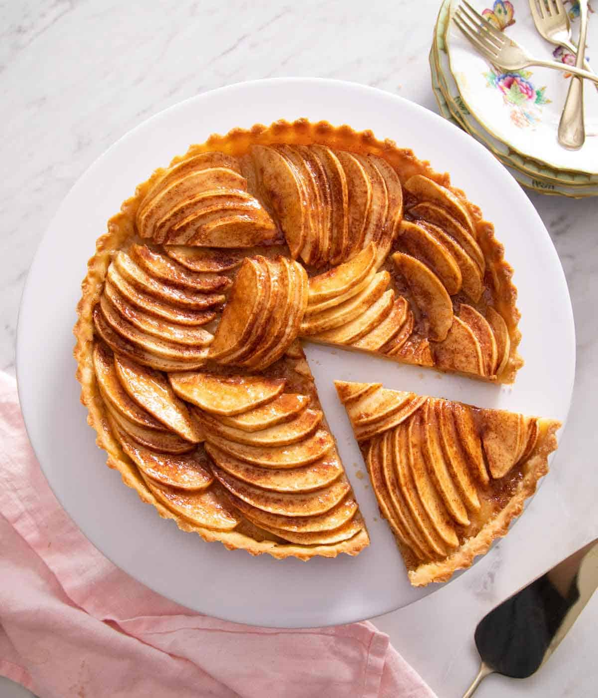 Overhead view of an apple tart with one slice cut out and move slightly away from it.