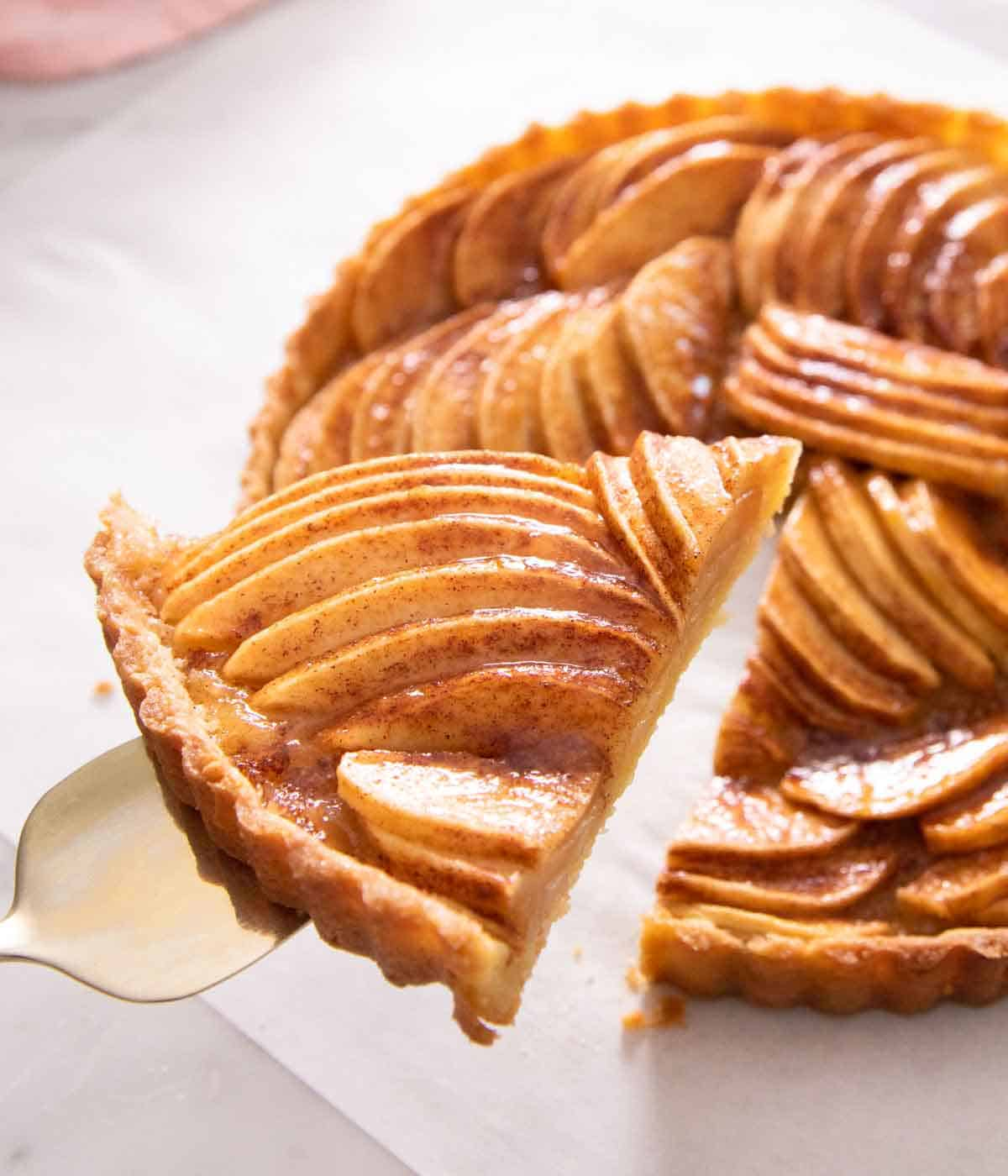 A slice of apple tart being lifted up from the tart.