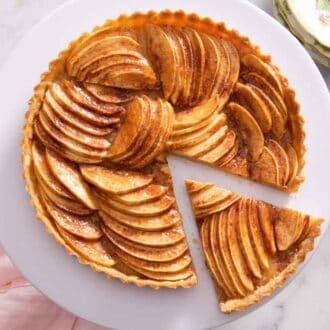 Overhead view of an apple tart with a slice cut and pulled slightly away from it.