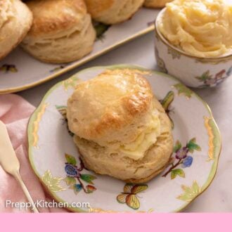 Pinterest graphic of a biscuit cut in half with butter spread on it with more biscuits in the back and a bowl of butter.