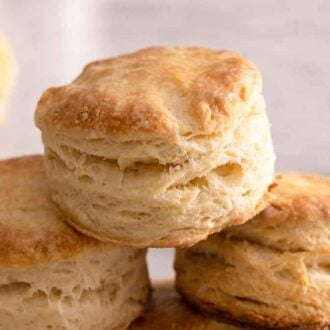 A pyramid of biscuits stacks on top of each other with a bowl of butter in the background.