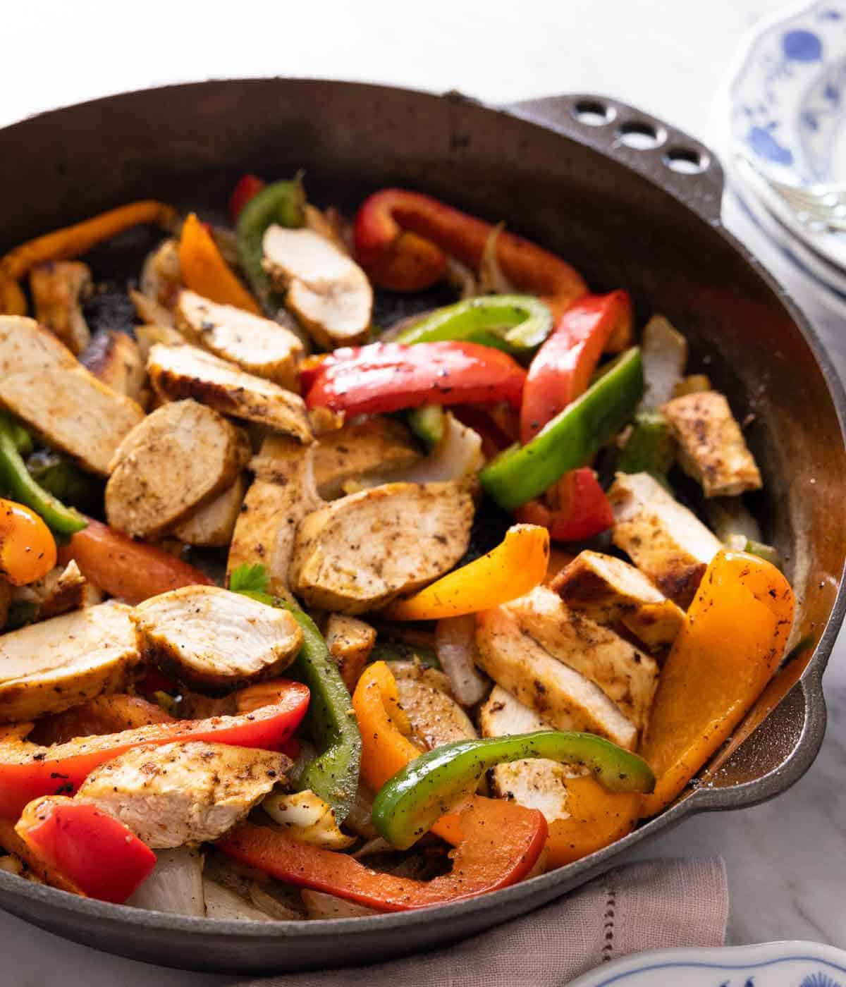 A cast iron skillet with chicken fajitas.