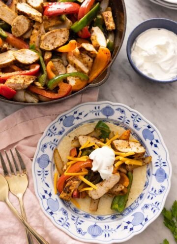A plate with chicken fajitas on a tortilla in front of a pan of fajitas.