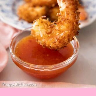 Pinterest graphic of a small bowl of sweet chili sauce with a coconut shrimp about to be dipped into it.