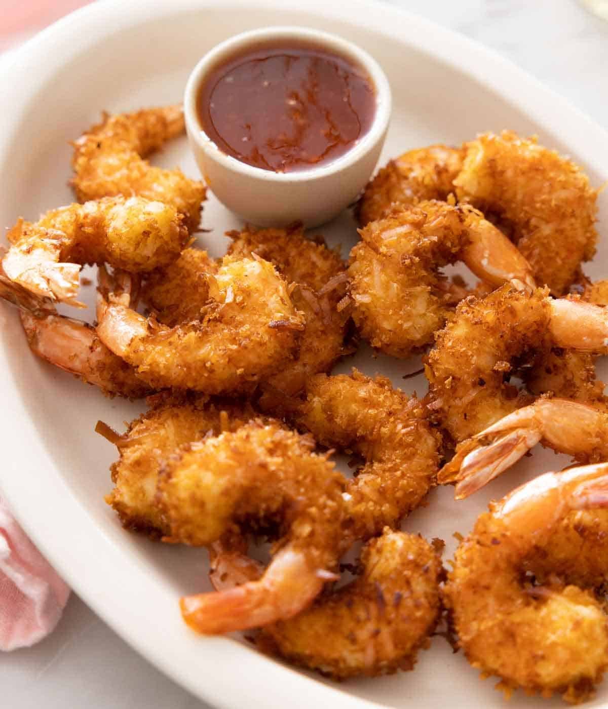 An oval platter with coconut shrimp and a dipping bowl of sauce.