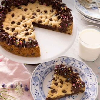 Pinterest graphic of a cookie cake on a cake stand with a slice cut and served on a plate in front.