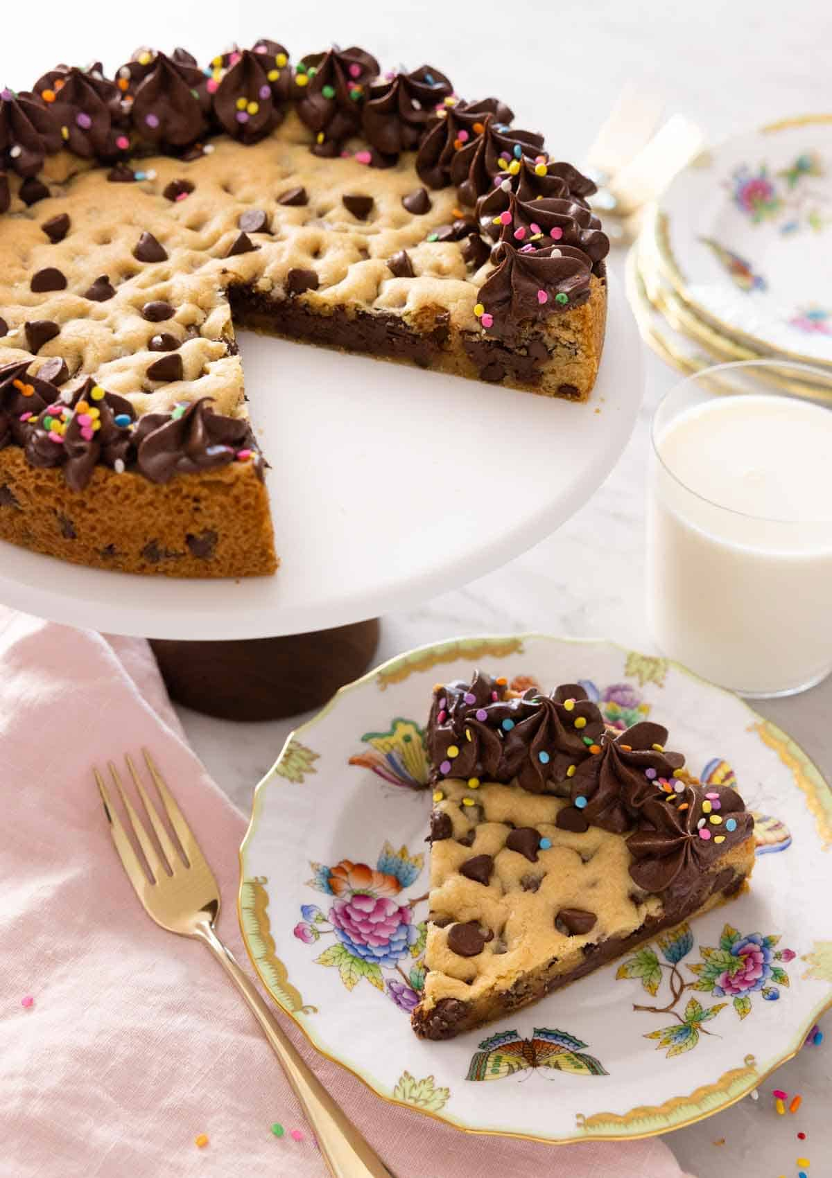 A cake stand with a cookie cake with a slice removed and placed on a plate.