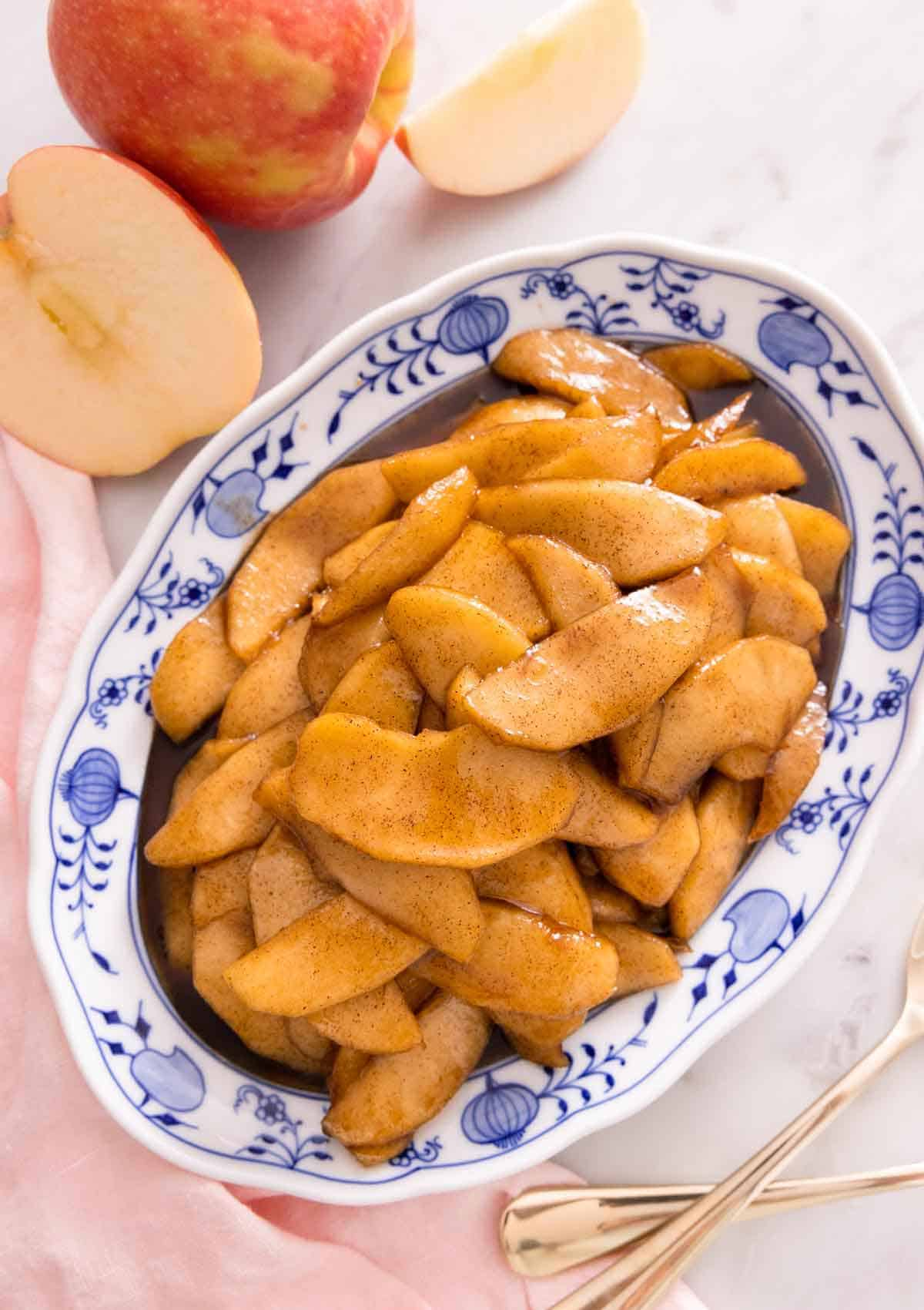An oval platter of fried apples beside a cut apple, pink linen napkin, and two forks.