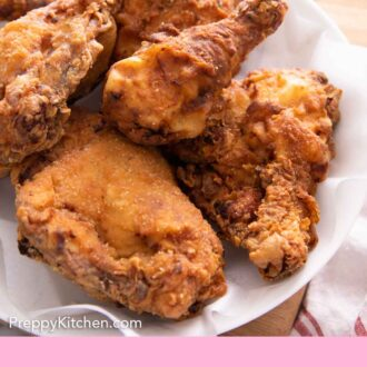 Pinterest graphic of a plate lined with a paper towel containing fried chicken.