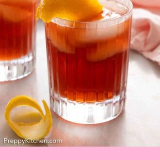 Pinterest graphic of a glass of Negroni with an extra orange peel in front.