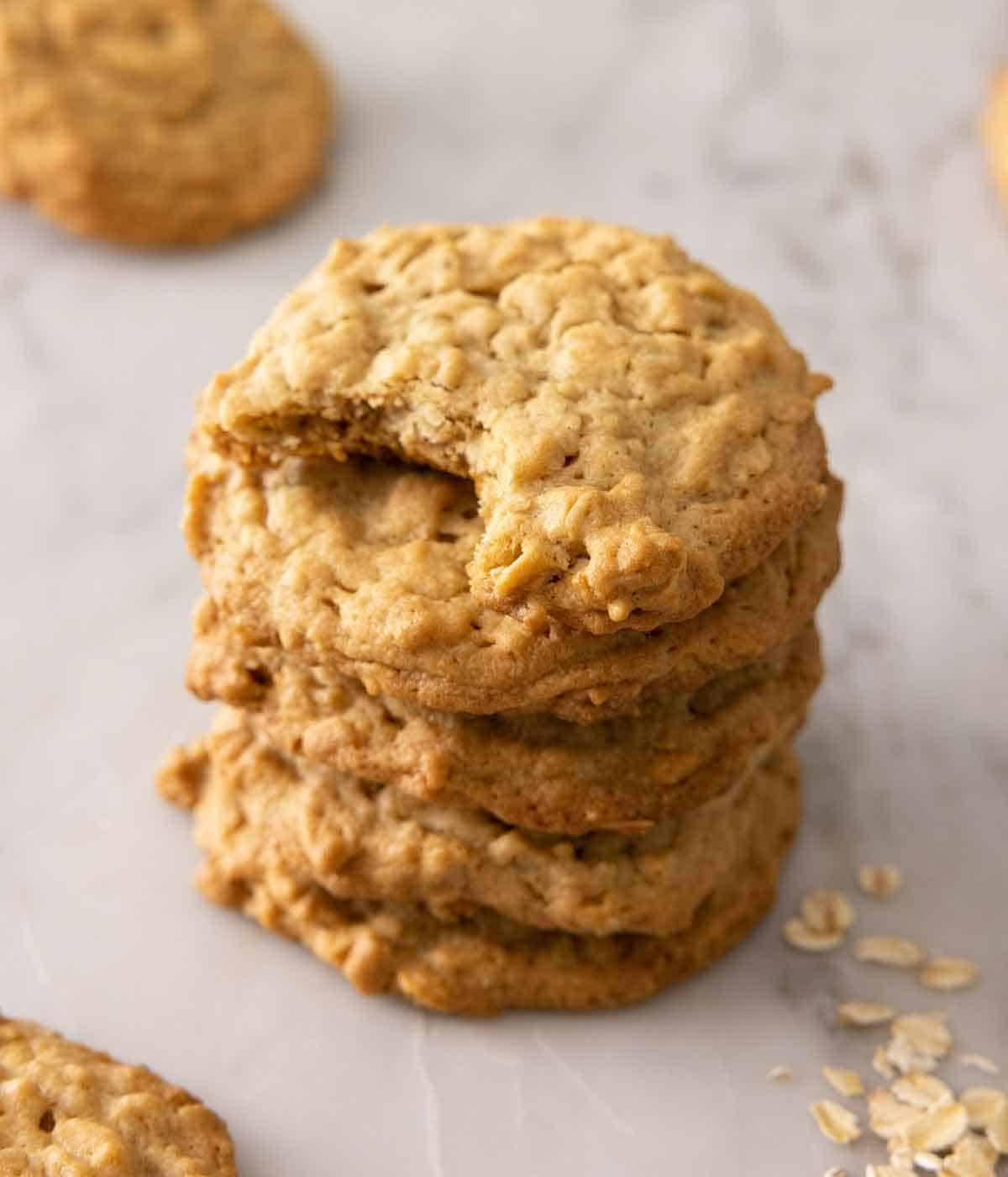 A stack of four peanut butter oatmeal cookies, the top one with a bite taken out.