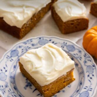 Pinterest graphic of a square slice of pumpkin cake on a plate with the rest of the cake in the background.