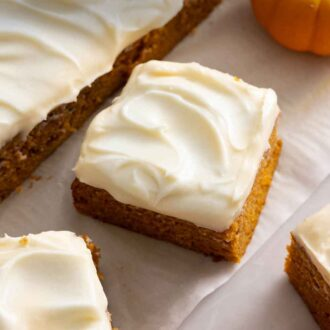 Pinterest graphic a pumpkin cake, cut into squares, with cream cheese on top.