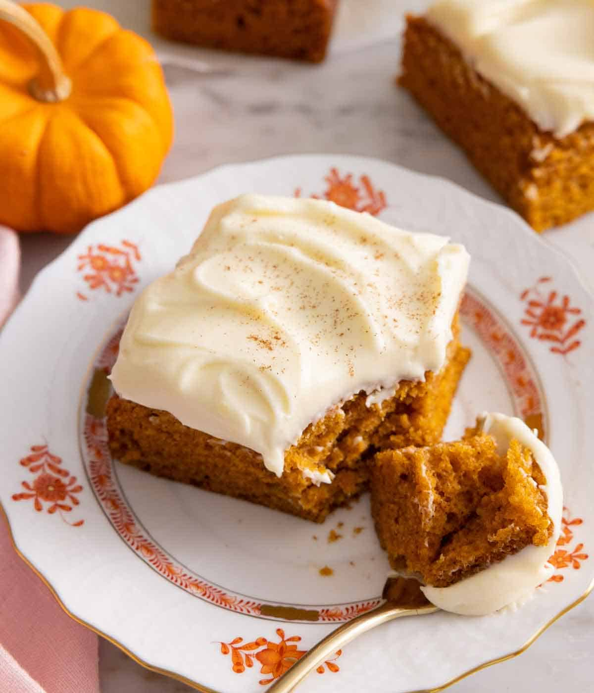 A square slice of pumpkin cake with a piece on a fork.