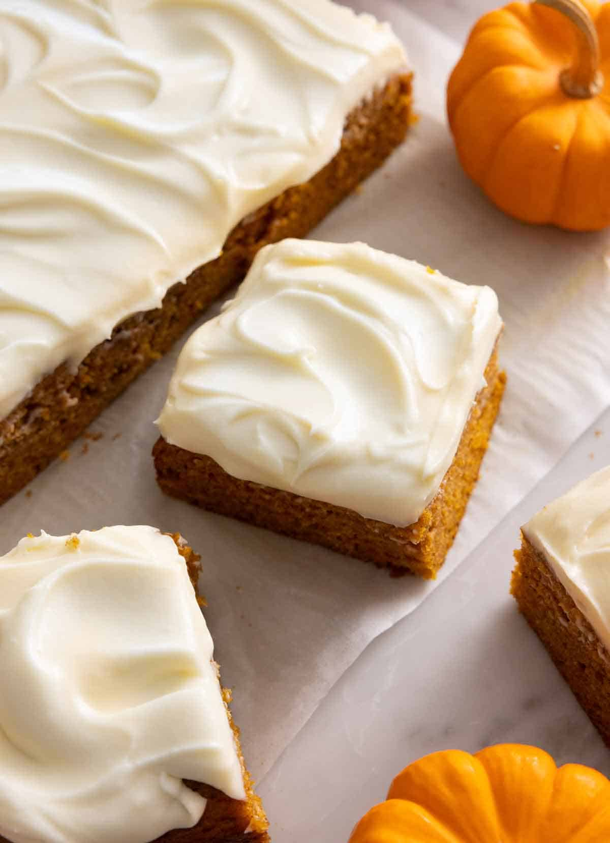 A pumpkin cake with 3 square slices cut and set beside it.