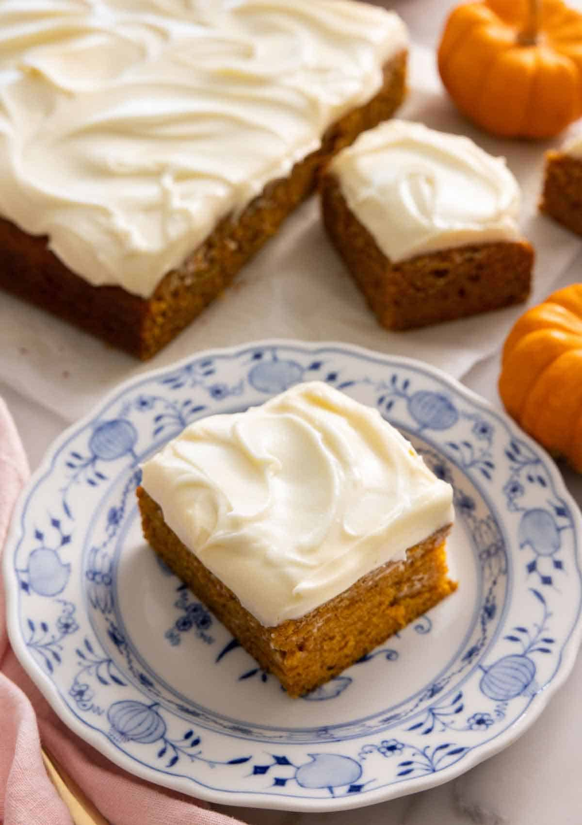 A square slice of pumpkin cake on a plate with the rest of the cake in the background.