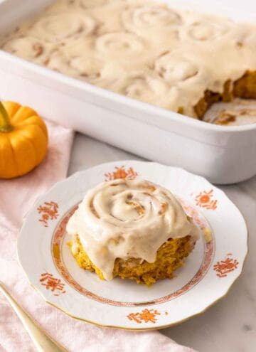 A plate with a single pumpkin cinnamon roll with cream cheese frosting on top in front of a baking pan with the rest.