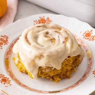 A plate with pumpkin cinnamon roll with cream cheese frosting on top.