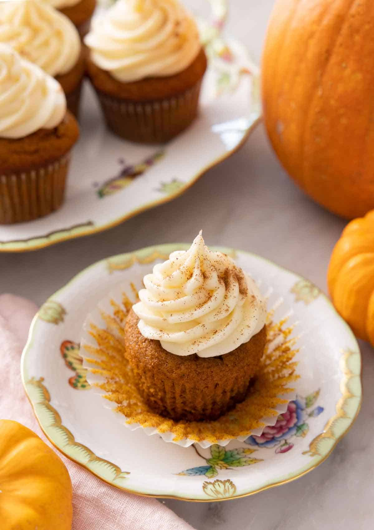 A plate with a pumpkin cupcake with cream cheese frosting on top with the cupcake liner pulled away.