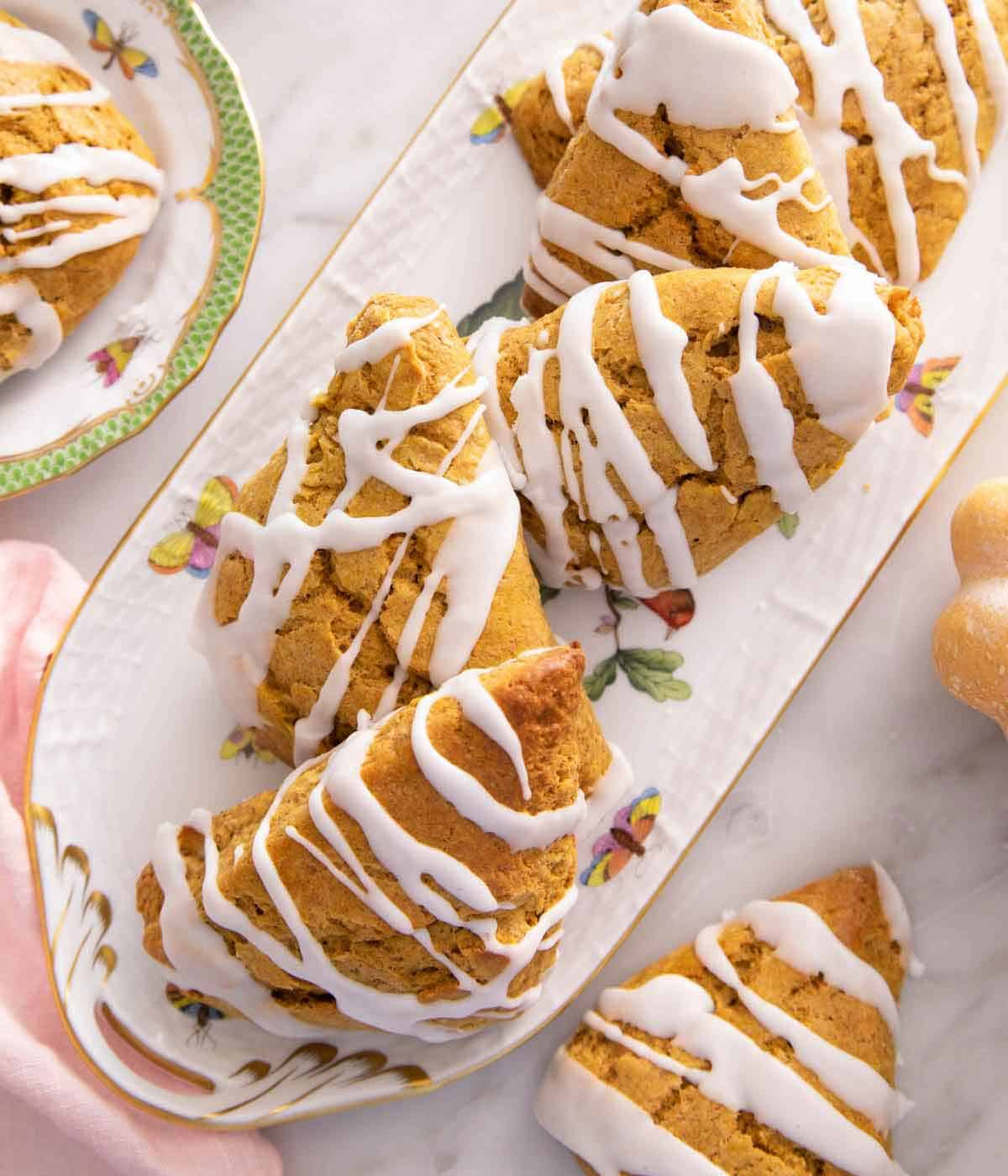 Overhead view of a platter of pumpkin scones with glaze drizzled on top.