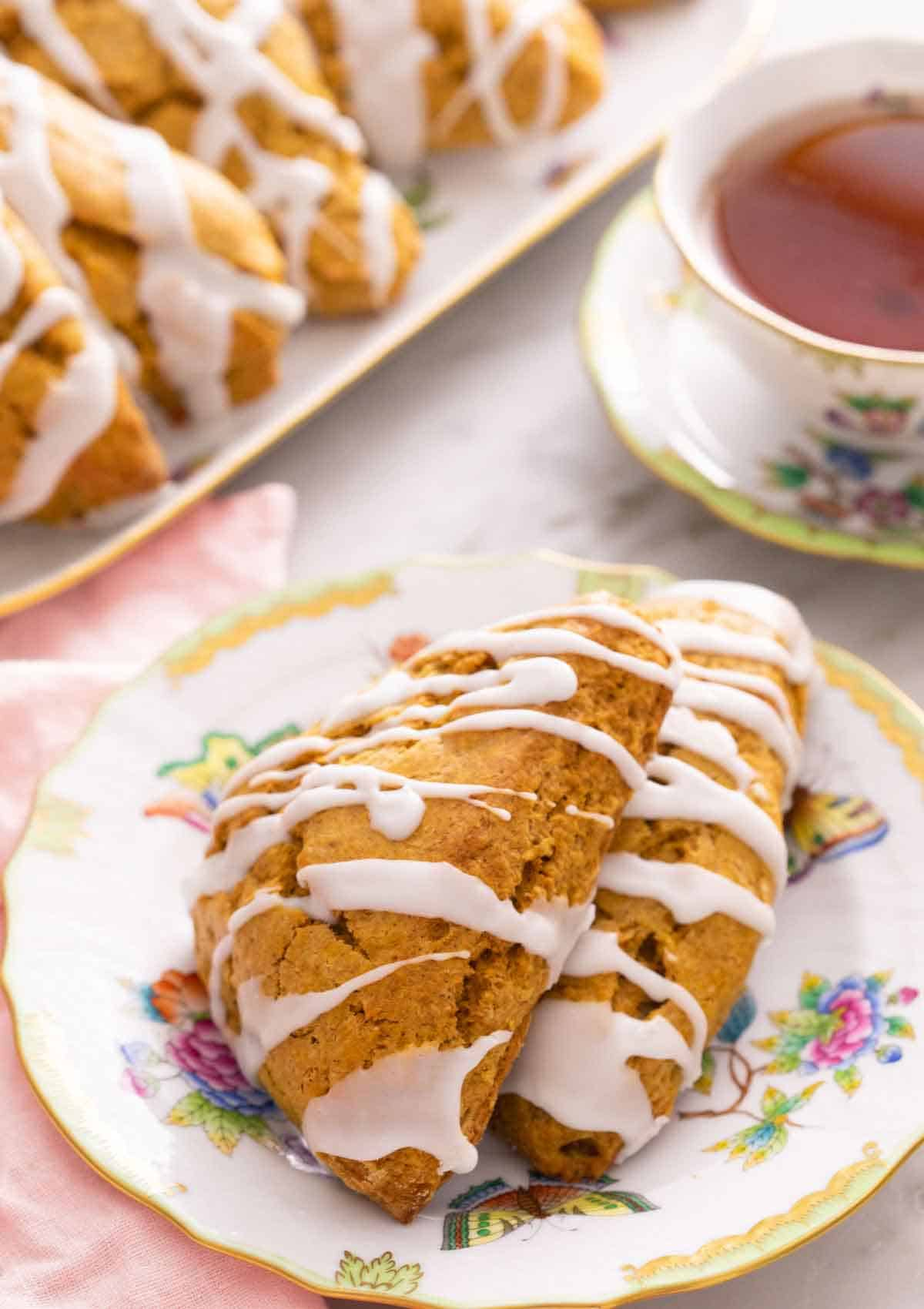 A plate with two pumpkin scones in front of a cup of tea and platter.