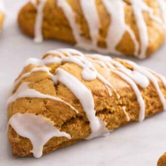 Many pumpkin scones on a marble counter with one in focus, in the middle.
