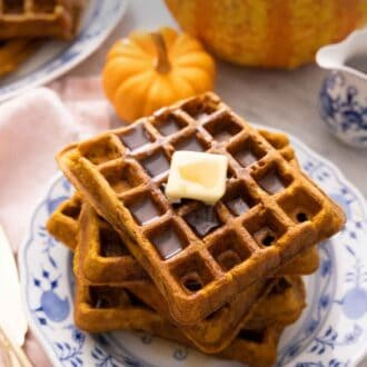 Pinterest graphic of a stack of pumpkin waffles with butter and syrup on top.