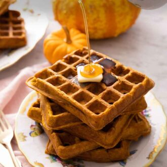 Pinterest graphic of a stack of five pumpkin waffles with a piece of butter on top and syrup poured on top.