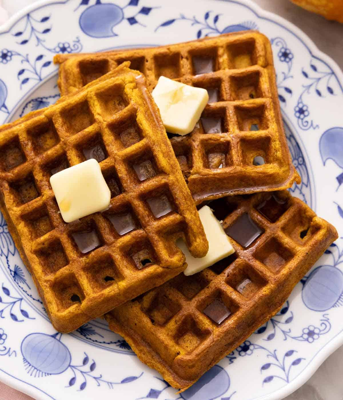 Overhead view of three pumpkin waffles with a knob of butter on top of each waffle.