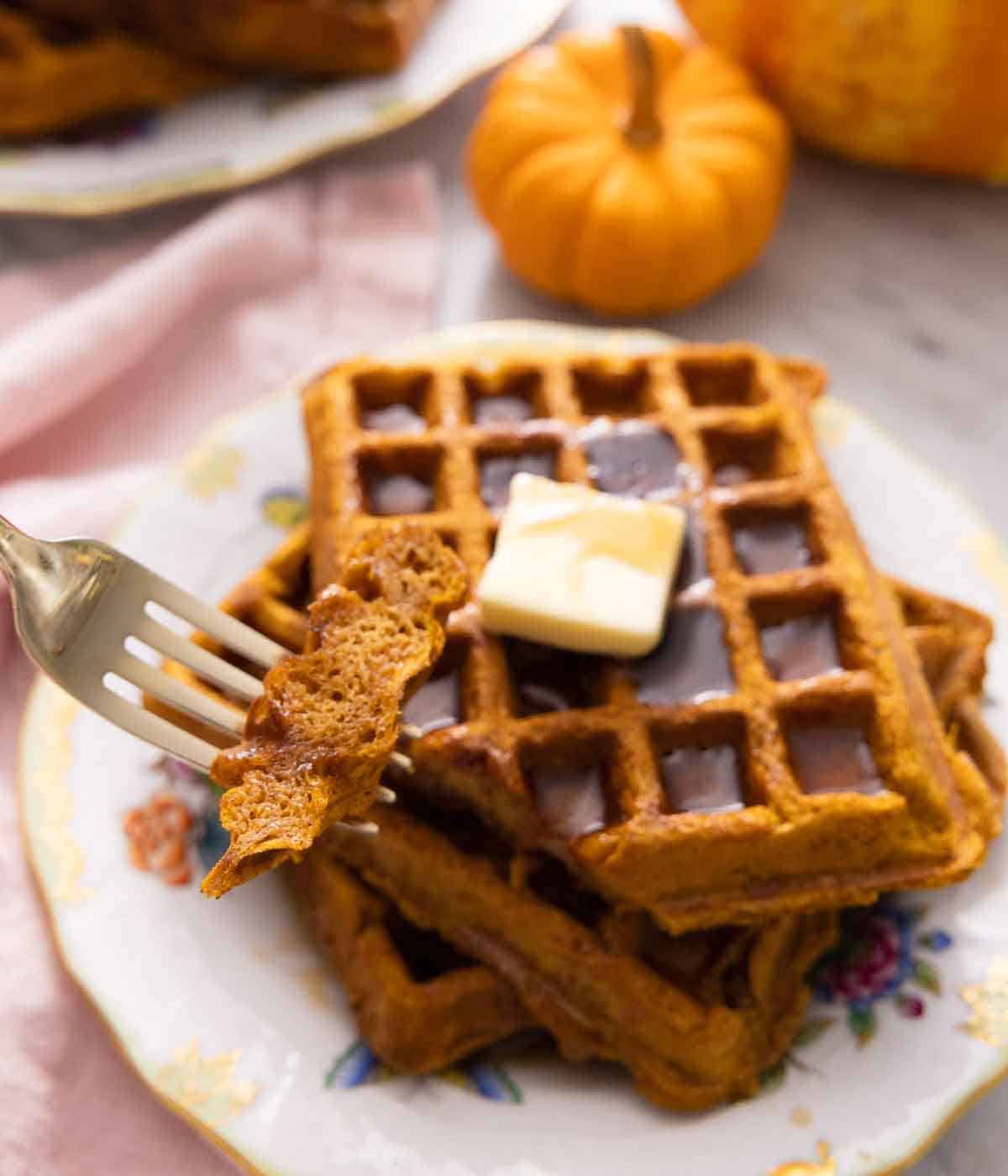 A fork with a piece of pumpkin waffle in front of a plate of waffles with syrup and butter.