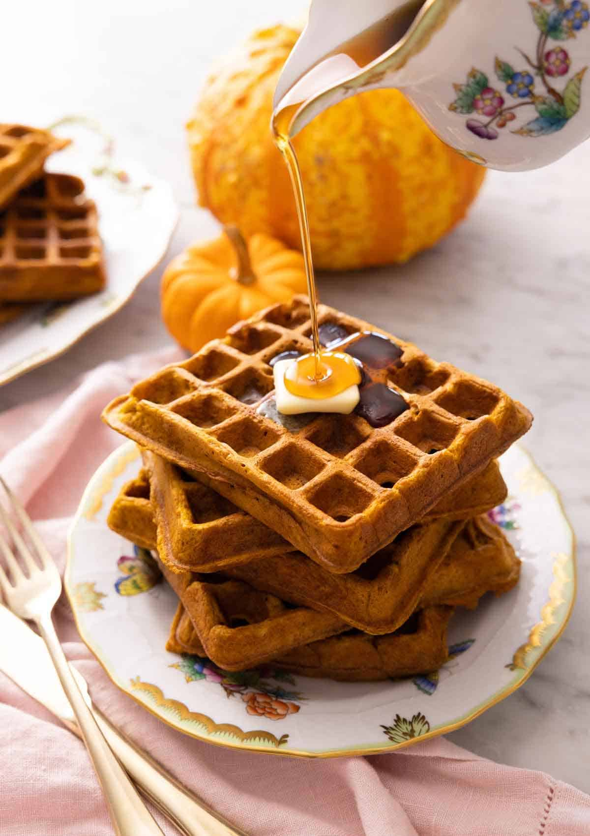 A plate with a stack of five pumpkin waffles with syrup poured on top.