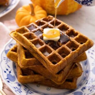 A stack of five pumpkin waffles with a piece of butter on top with syrup being poured on top.